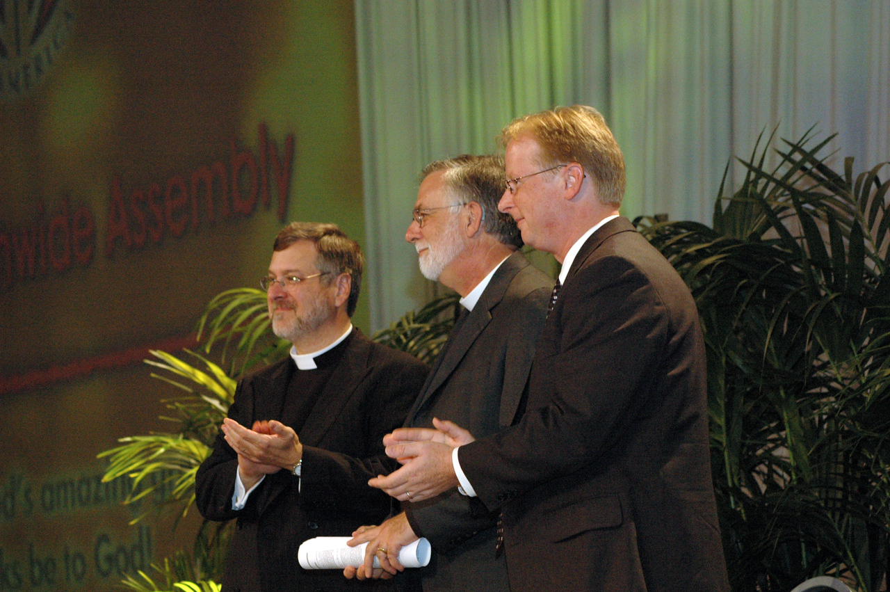 The Rev. Paul Schreck (ELCA), The Rev. Gary Harke (Moravian Church) and Dr. Michael Trice (ELCA) applaud after the assembly passed a recommendation to extend full communion between the ELCA and the Moravian Church in America to include the Alaska Province and the East West Indies Province of the Moravian Church in America.