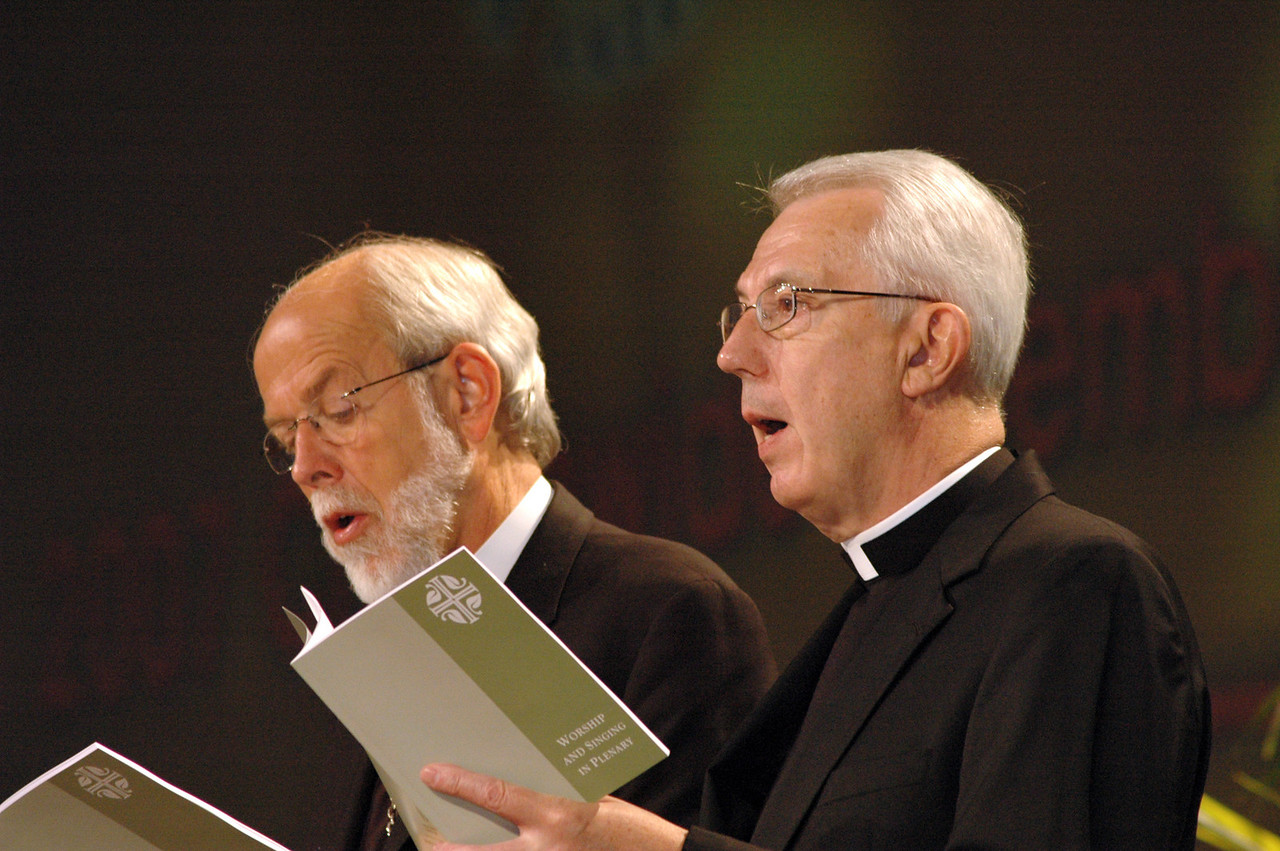 """ELCA Presiding Bishop Mark Hanson and ELCA Secretary Lowell Almen join the assembly in singing """"The Church's One Foundation"""" following Almen's report to the assembly."""