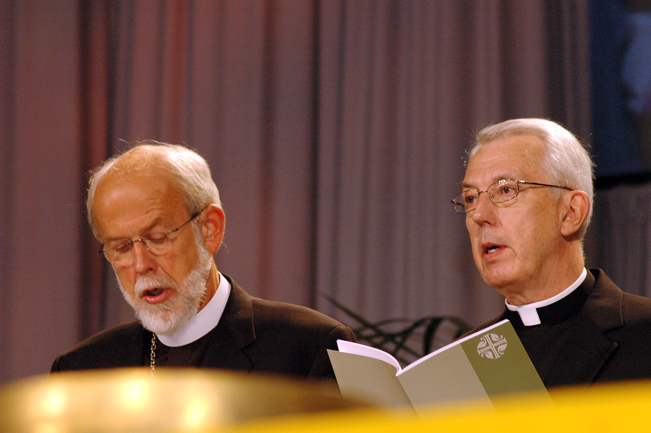 "ELCA Presiding Bishop Mark Hanson and ELCA Secretary Lowell Almen join the assembly in singing ""The Church's One Foundation"" following Almen's report to the assembly."