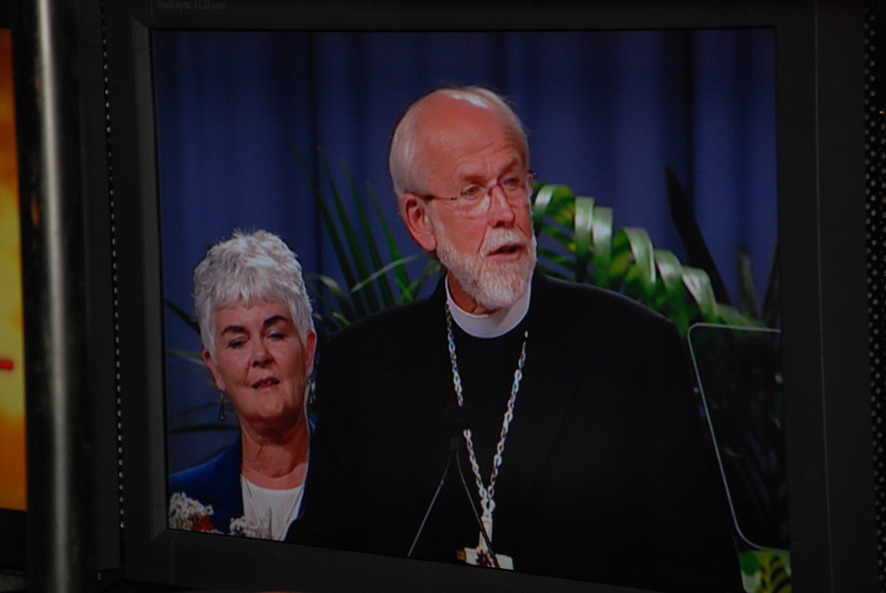 On television, Ione and Bishop Mark Hanson addressing the voting Members, after being re-elected for his second term.