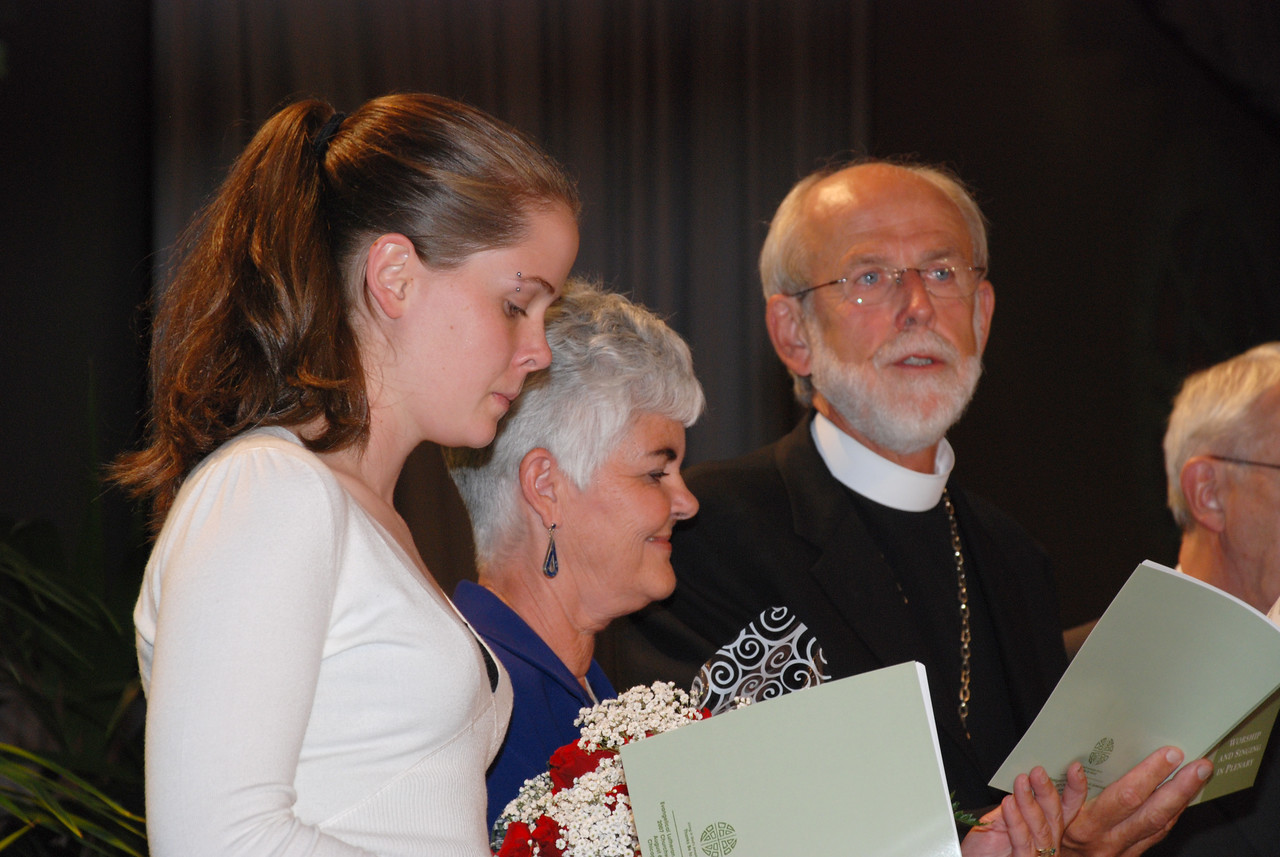Ione and Elizabeth Hanson on stage during closing prayer with newly elected Bishop Hanson on Tuesday's Plenary session.