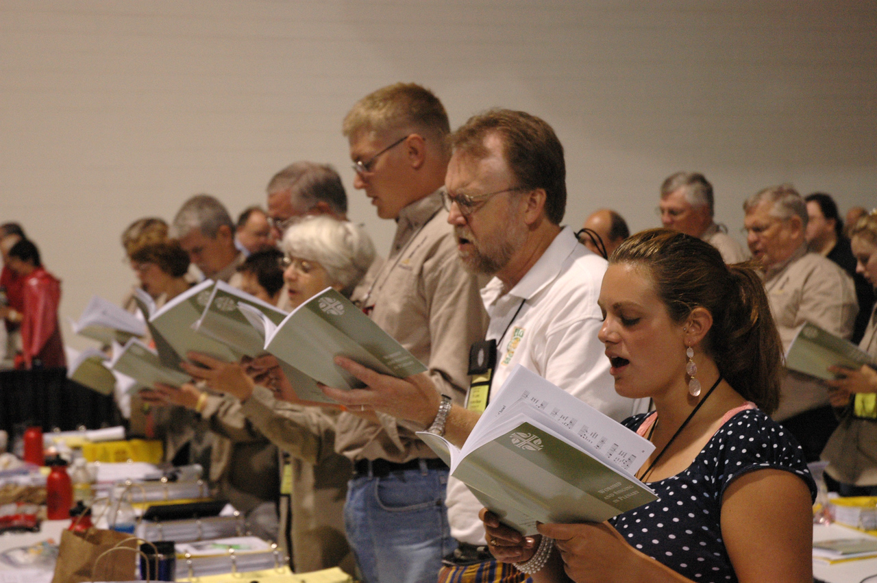 Plenary session four opens with prayer and hymn.