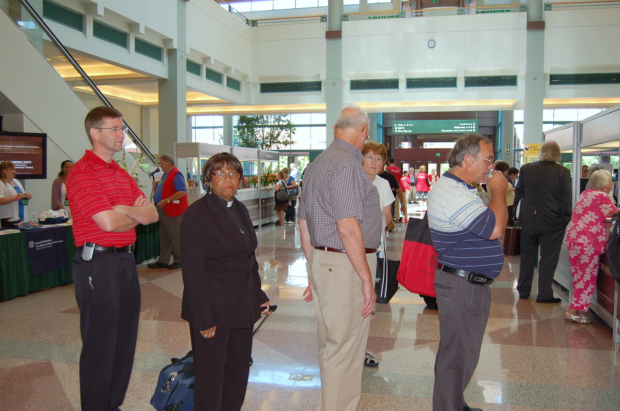 The Rev. Jonathan Bull from the Metropolitan Synod of New York (left) and the Rev. Rosalind Brathwaite of First Lutheran Church, Belafonte, Ohio, wait in line to pick up their voting member registration materials. They are among the 1,045 voting members from 65 synods and 10,396 congregations serving on behalf of the 4,633,887 baptized members of the Evangelical Lutheran Church in America.
