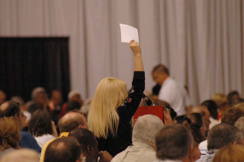 A voting member holds up a white card to indicate that she is calling for a motion.