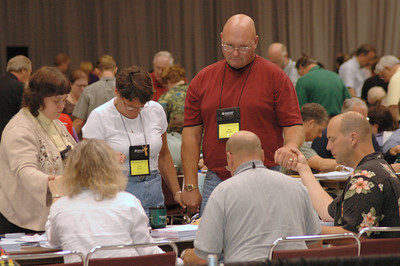 Voting members pray after resolution three of the Ministry Policy Recommendation passed.