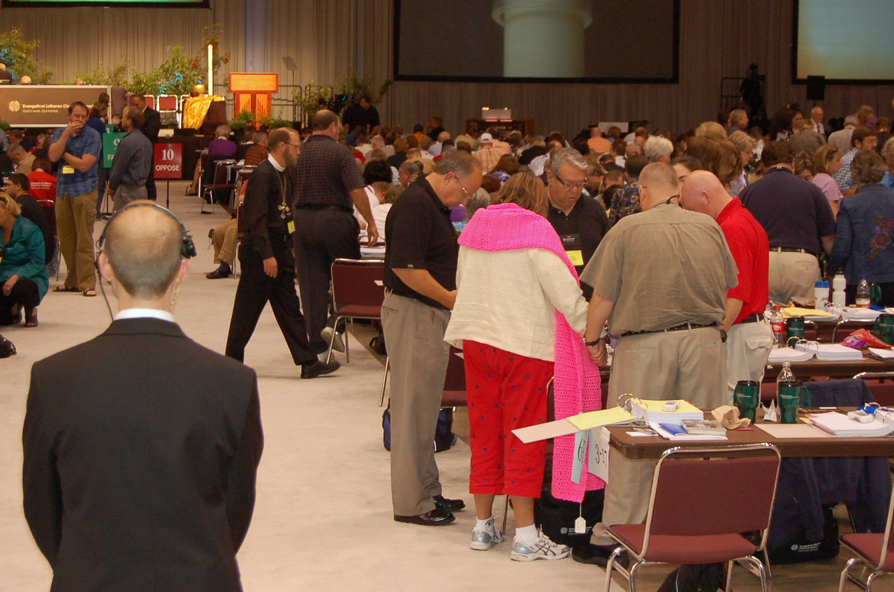 An impromtu prayer during plenary session nine. Scott Hendrickson, director for marketing, public relations and creative services, is seen in the foreground.