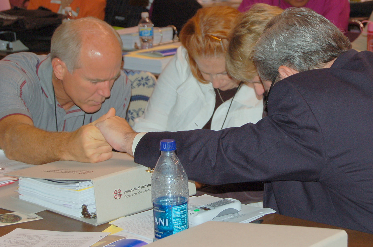 Voting members pray during a plenary session.