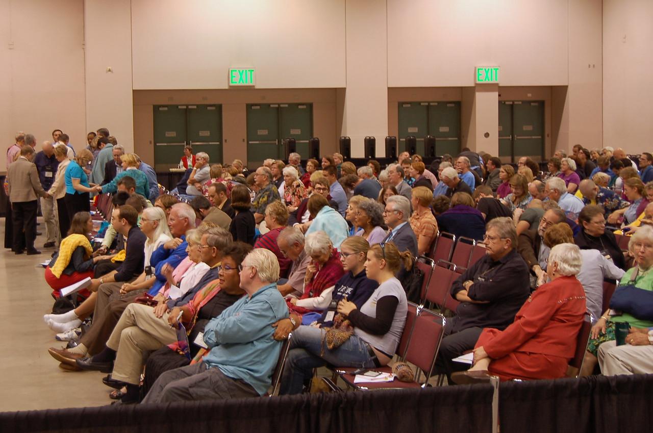 Visitors to plenary session nine. An impromtu prayer during plenary session nine may be seen in the back.