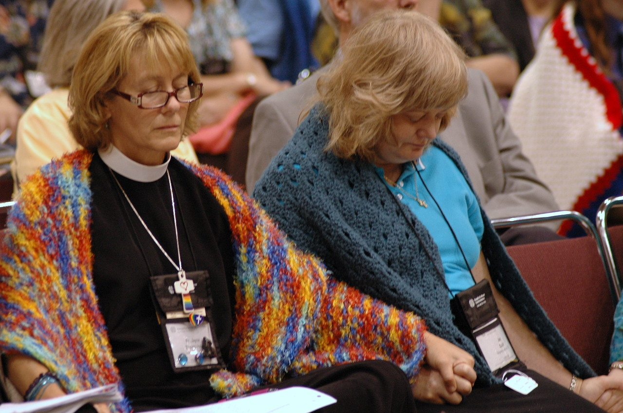 Visitors pray during plenary session eight.