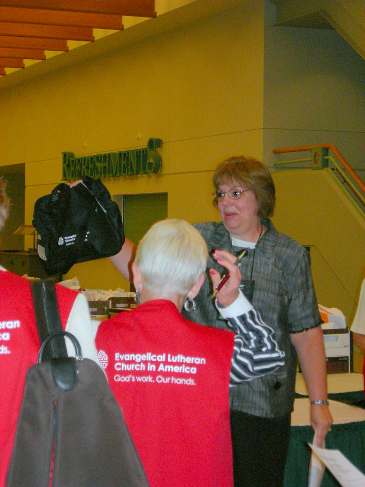 Gail Schroeder, meeting planner, instructs volunteers who will assist in the registration area.
