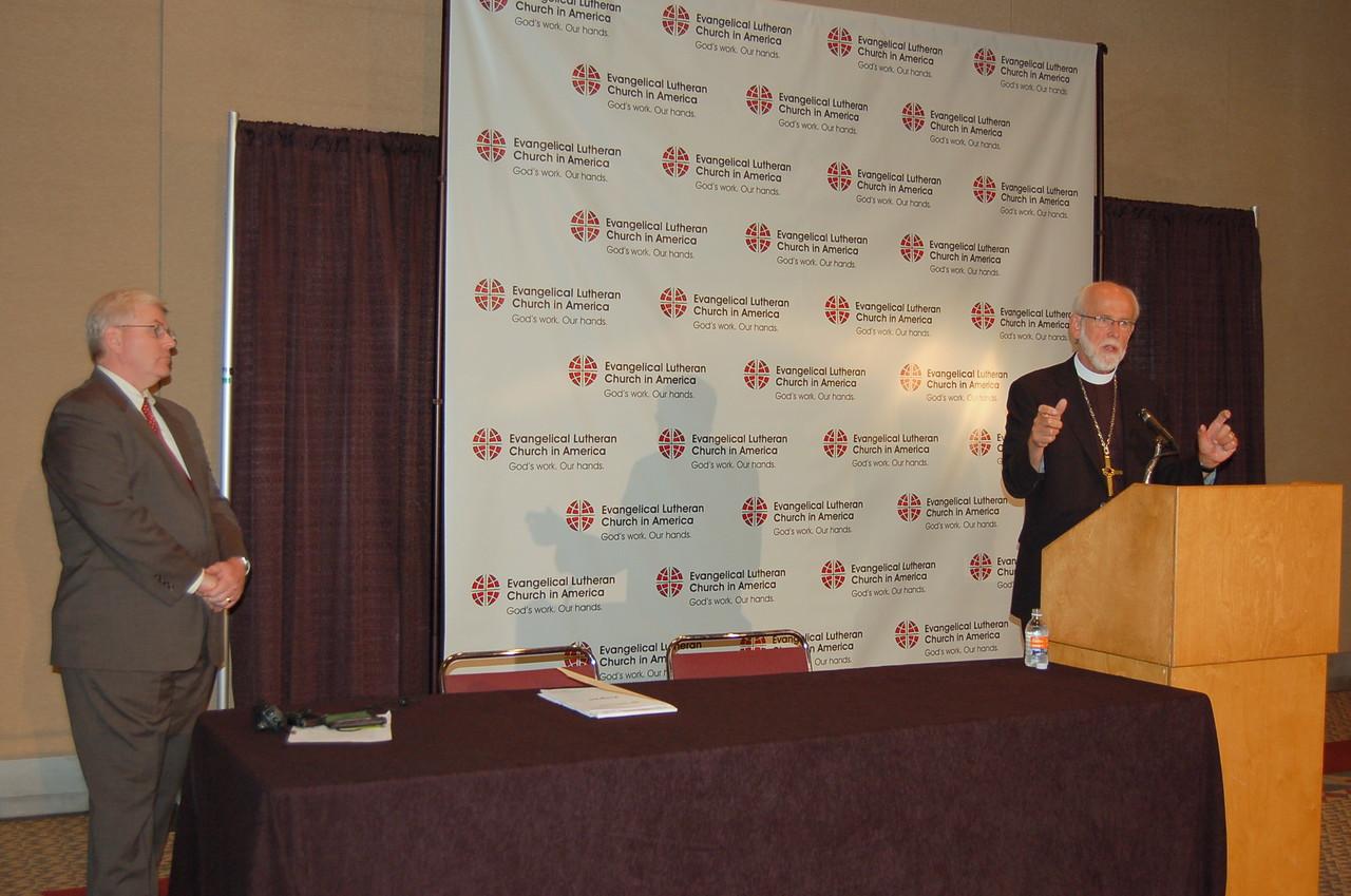 Presiding Bishop Mark S. Hanson speaks as John Brooks, ELCA news director, looks on.