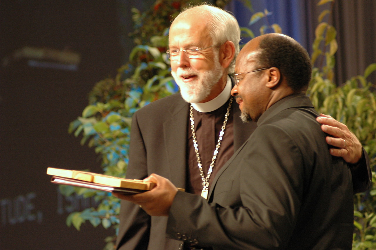 Presiding Bishop Mark S. Hanson offers Dr.Ishmael Noko, secretary of the Lutheran World Federation, a gift upon his retirement.