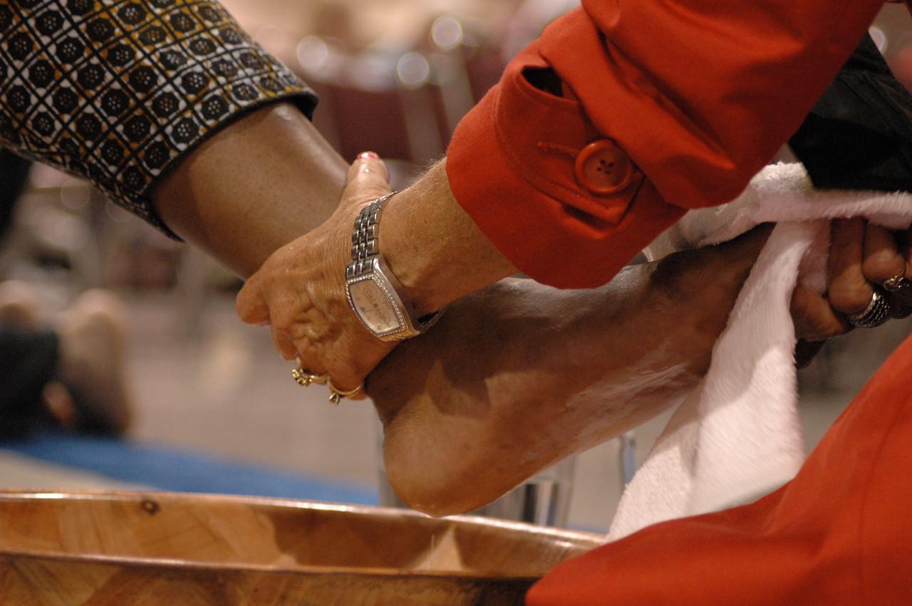 Drying a worshiper's foot.