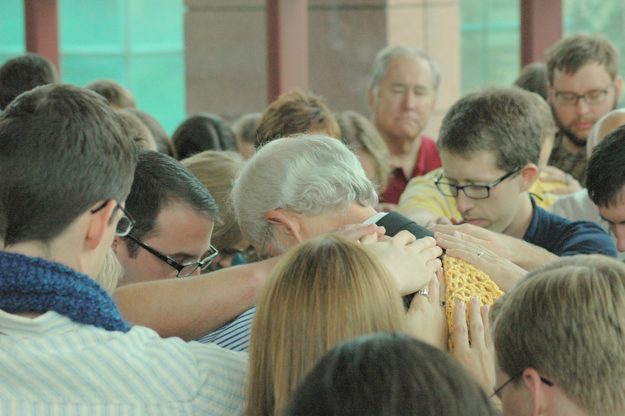Young Rostered Leaders lay hands of blessing on Bishop Hanson.