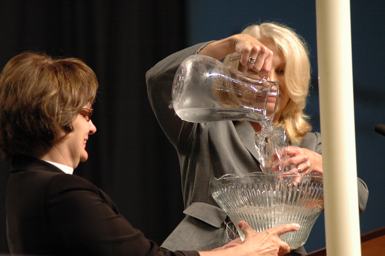 In her part of the Lutheran Malaria Initiative report, ELCA Foundation president Cynthia Halvorson demonstrates the reality of overflowing abundance in the ELCA, not a glass half empty, or even half full.  LMI Coordinator Andrea DeGroot -Nesdahl assists with the object lesson.