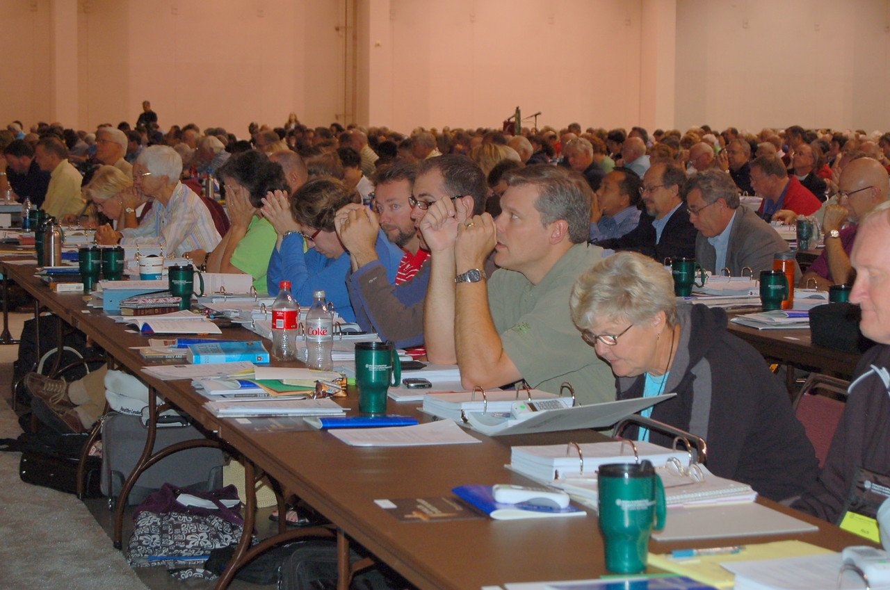 Voting members pray before voting on the proposed social statement.