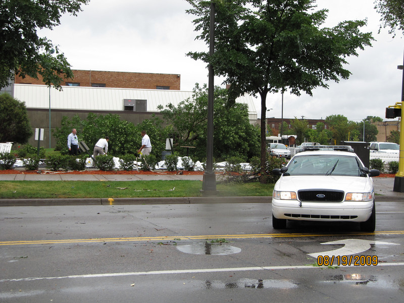 Police block a street to allow workers to begin cleaning up damage caused by the tornados.