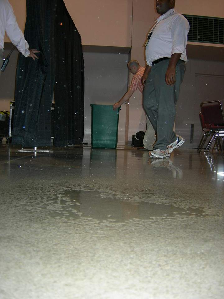 Rain from the storm-damaged roof collects on the floor.