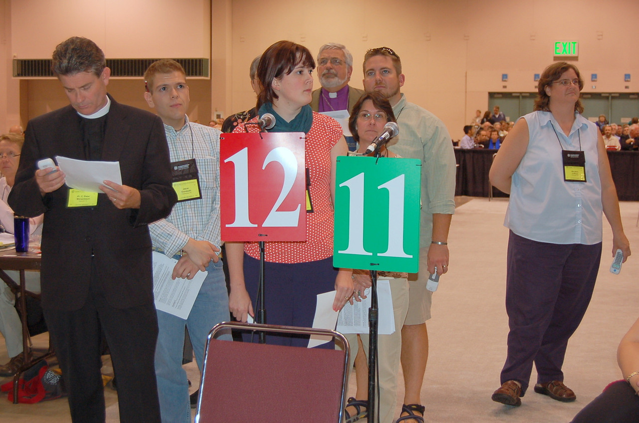 Voting members wait their turn to speak to the assembly.