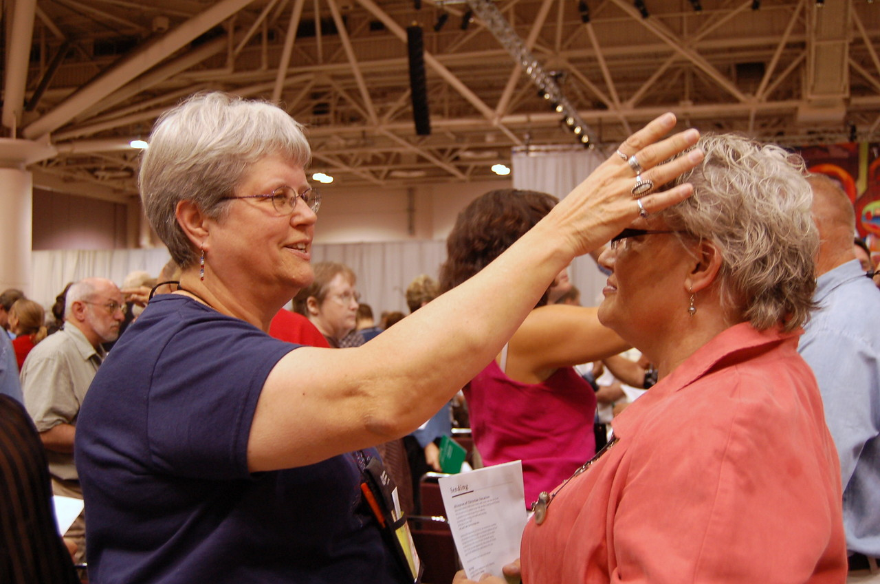Worshipers mark one another with the sign of the cross.