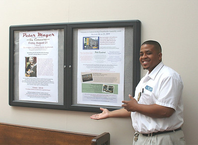 A convention center employee shows the Peter Mayer posters.