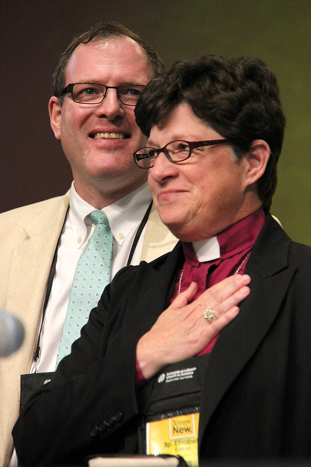The Rev. Elizabeth A. Eaton, bishop-elect, comes to the stage with her husband, the Rev. Conrad Selnick.