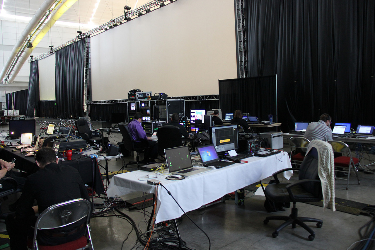 Production and technical staff work behind the stage.