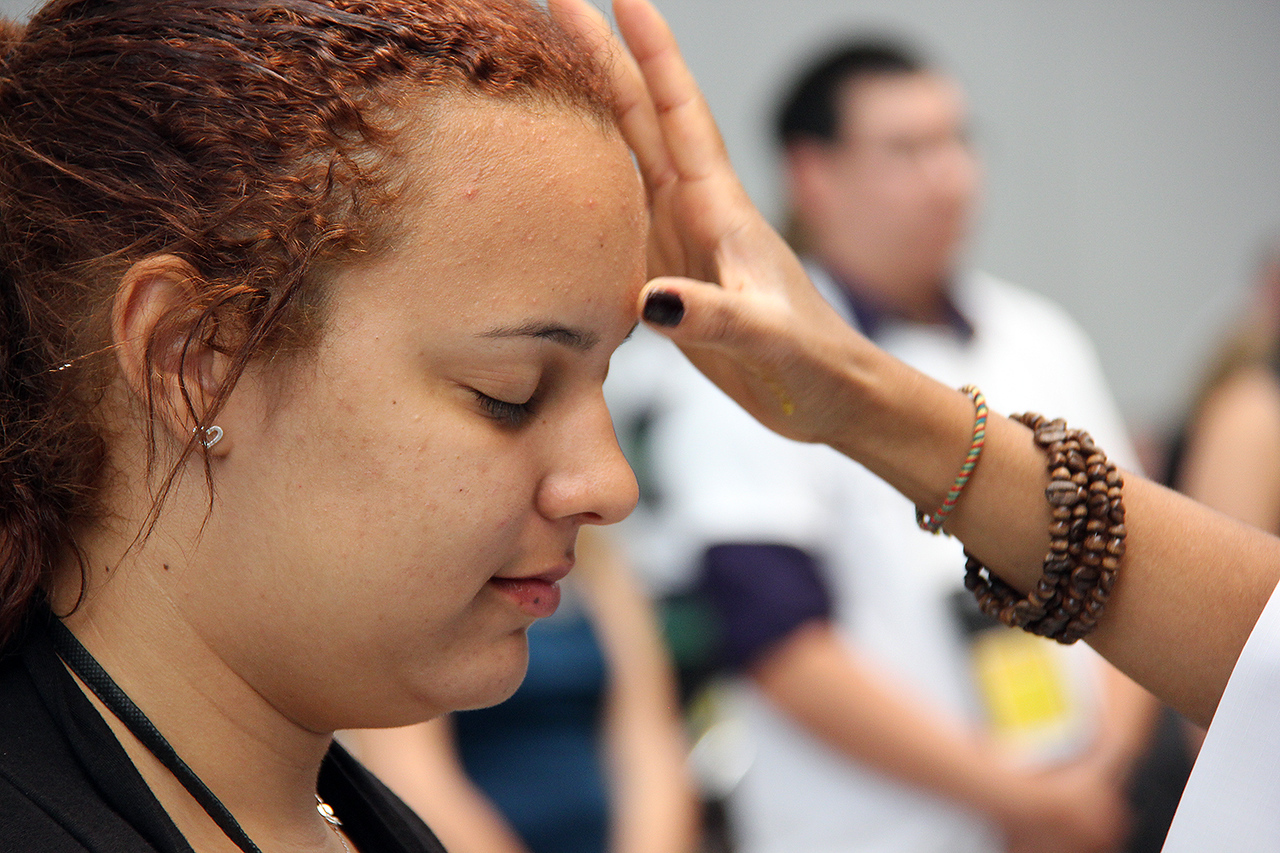Cheyenne Williams is marked with the sign of the cross during worship.