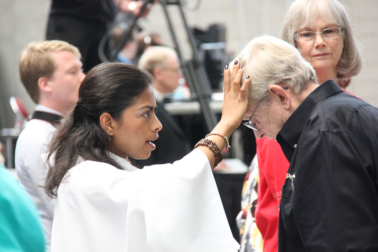 Assembly attendees are marked with the sign of the cross during worship.