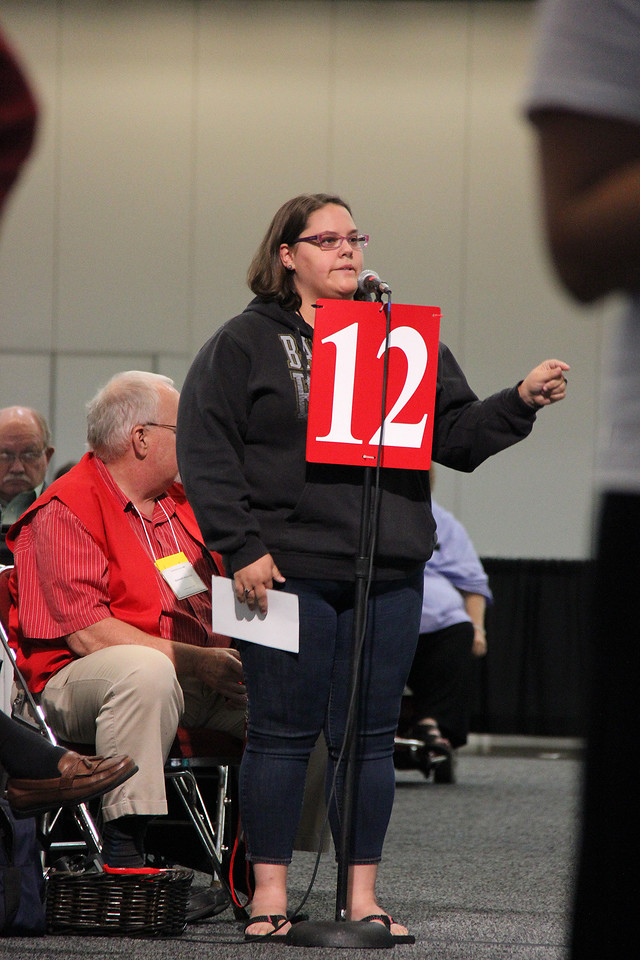A voting member speaks against a motion.