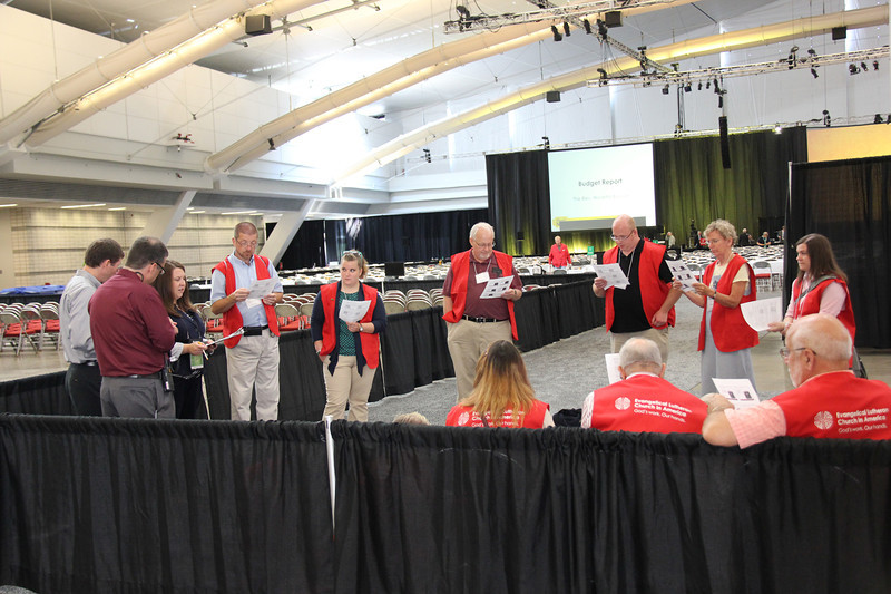 Laury Rinker instructs the volunteers who will be working on the plenary floor.