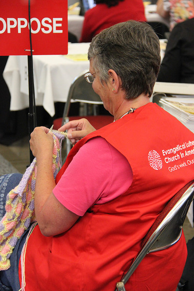 A volunteer takes a break to knit.