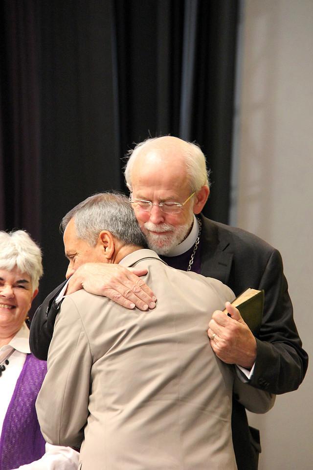 Carlos E. Peña, vice president of the ELCA, embraces Presiding Bishop Mark S. Hanson while Mrs. Ione Hanson looks on.