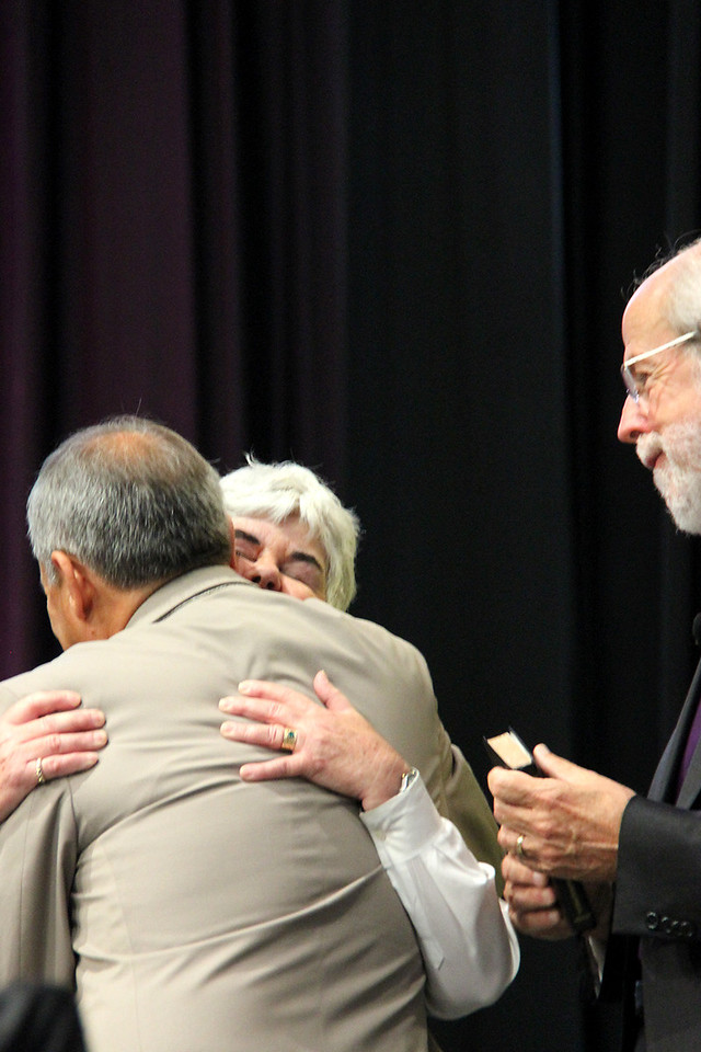 Carlos E. Peña, vice president of the ELCA, embraces Mrs. Ione Hanson while Presiding Bishop Mark S. Hanson looks on.