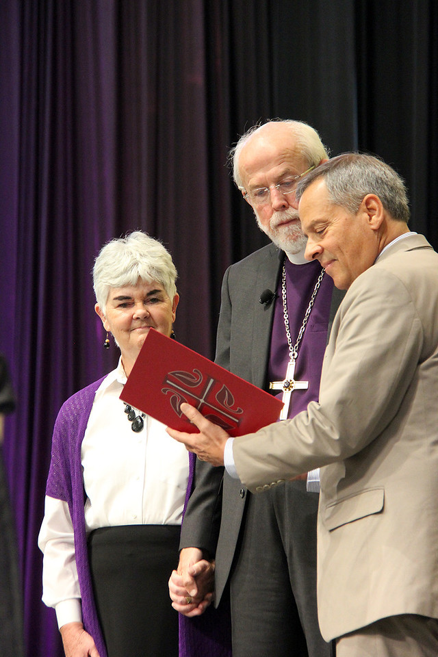 Carlos E. Peña, vice president of the ELCA, asks the Assembly to join in a liturgy of thanksgiving for Presiding Bishop Mark S. Hanson's ministry in the life of this church. Mrs. Ione Hanson stands by Presiding Bishop Hanson's side.