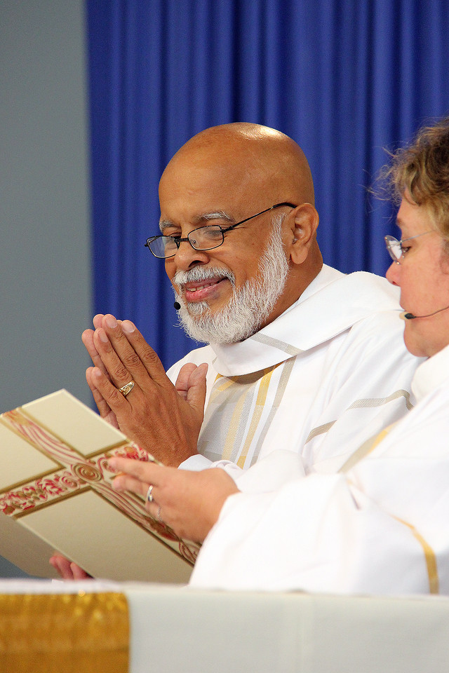 The Rev. George Cruz-Martinez is assisted by Adriana Johnson during worship.