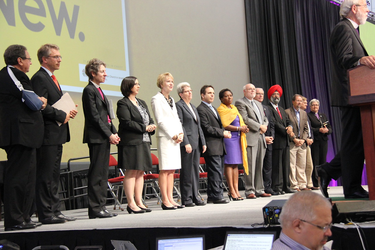Ecumenical and interreligious guests present for the assembly join Presiding Bishop Mark S. Hanson on the stage.