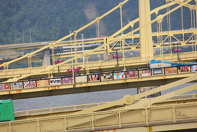 Assembly voting members, guests and volunteers enjoy a view of the Allegheny River next to the David L. Lawrence Convention Center. An art project in Pittsburgh, consisting of 600 colorful knitted quilts, decorates the Andy Warhol Bridge.