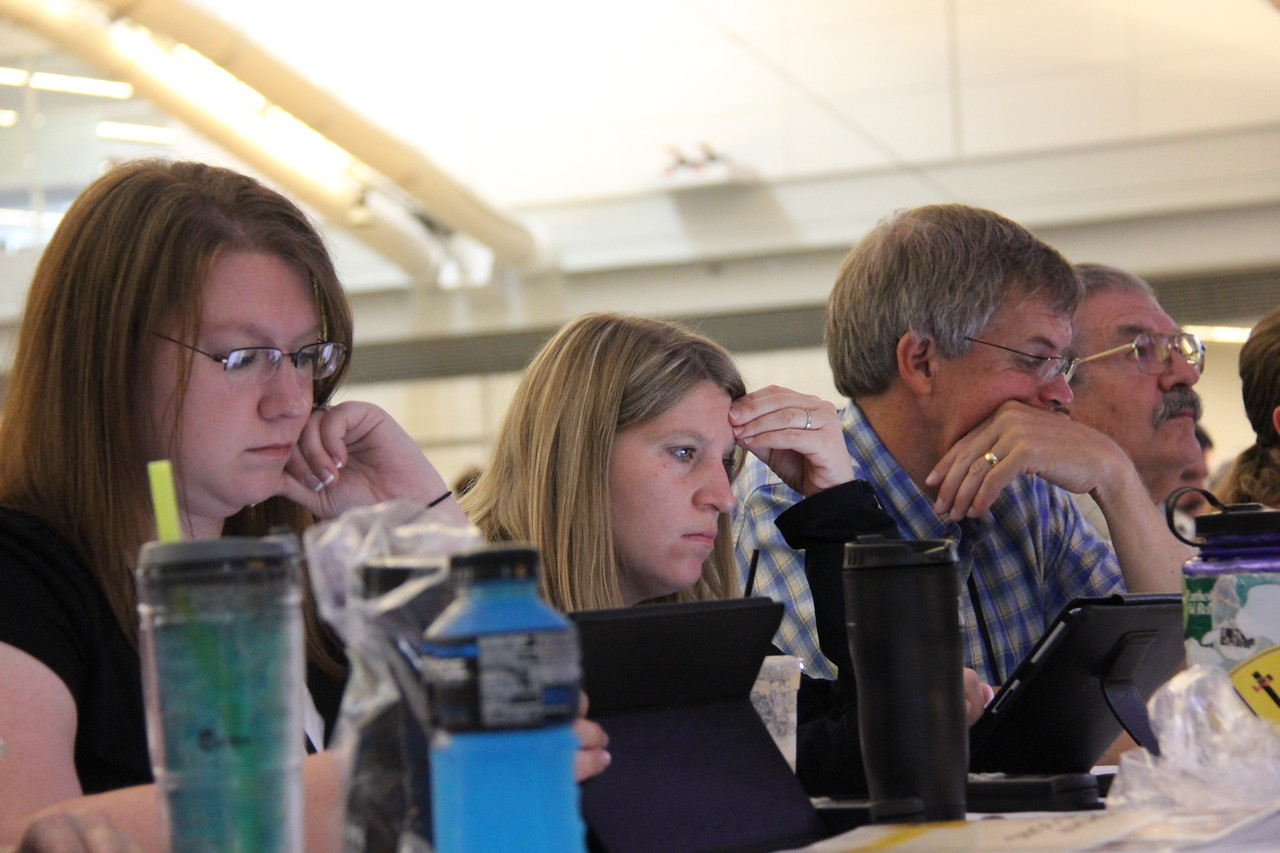 Voting members review their Guidebook during the second plenary on Tuesday morning, August 13.