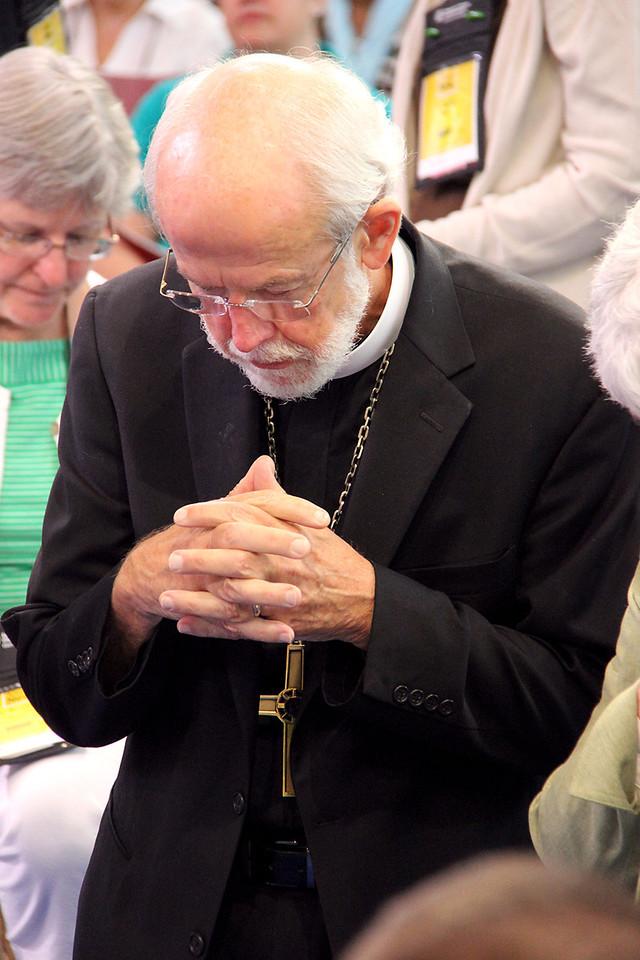 Presiding Bishop Mark Hanson kneels in prayer by the cross during worship.