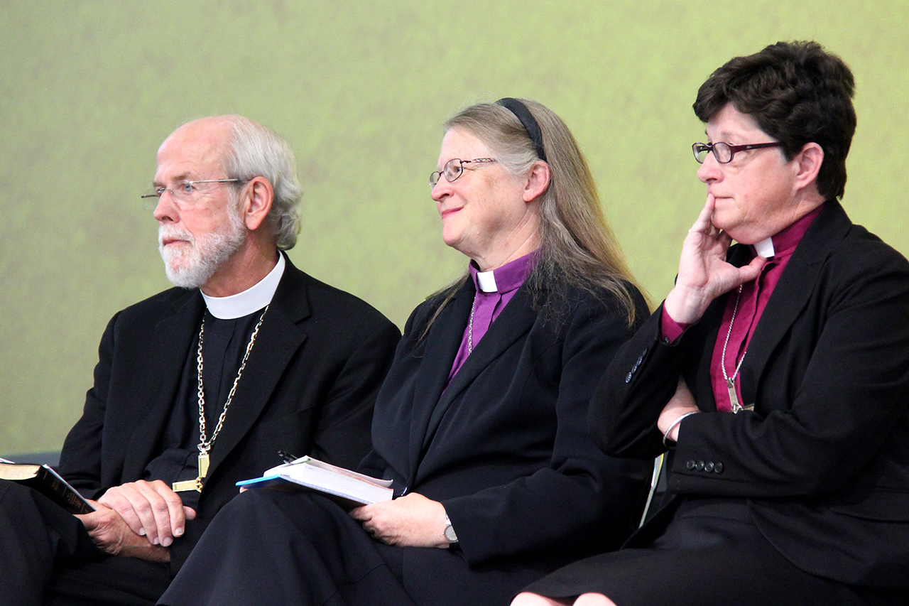 Presiding Bishop Mark Hanson, Bishop Jessica Crist and Bishop Elizabeth Eaton, nominees for presiding bishop, wait to address the Assembly.