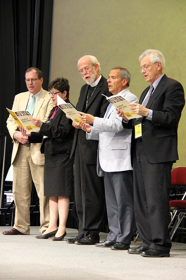 The Rev. Conrad Selnick, the Rev. Elizabeth A. Eaton, bishop-elect, Presiding Bishop Mark S. Hanson, David Swartling, secretary of the ELCA and Carlos E. Peña, vice president of the ELCA sing during the plenary.