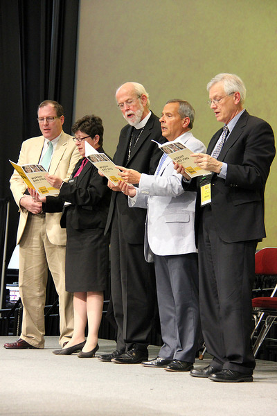 The Rev. Conrad Selnick, the Rev. Elizabeth A. Eaton, bishop-elect, Presiding Bishop Mark S. Hanson, David Swartling, secretary of the ELCA and Carlos E. Peña, vice president of the ELCA sing during the plenary.