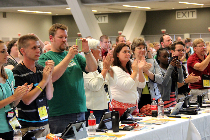 Voting members take photos and applaud during the election for presiding bishop.