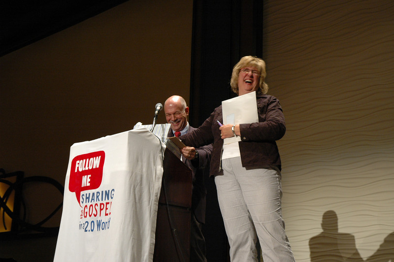 The Rev. Eric C. Shafer, Senior Vice-President of Philanthropy and Faith Community Relations, Odyssey Networks, and Sue Rothmeyer, Associate Executive Director for Youth and Young Adult Ministries, Vocation and Education, as she selects the winner of the smart phone