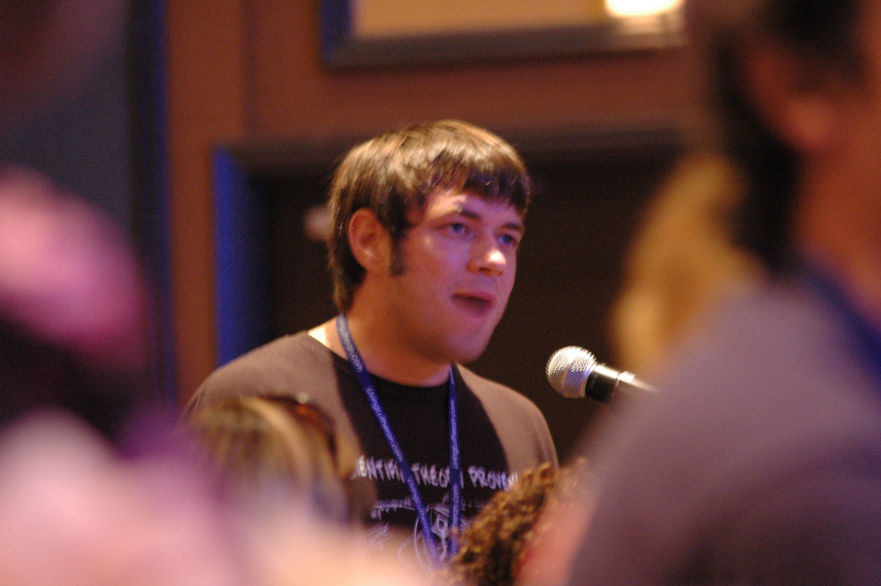 A young adult participant asks Bishop Hanson a question