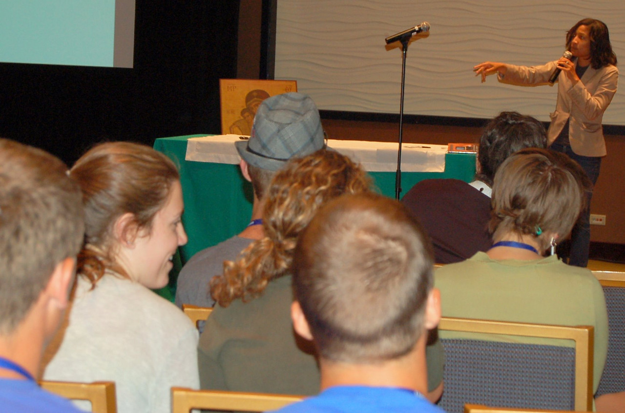 Young adults listen to Yvonne Gilmore-Essig, spoken word artist at the Community Cafe