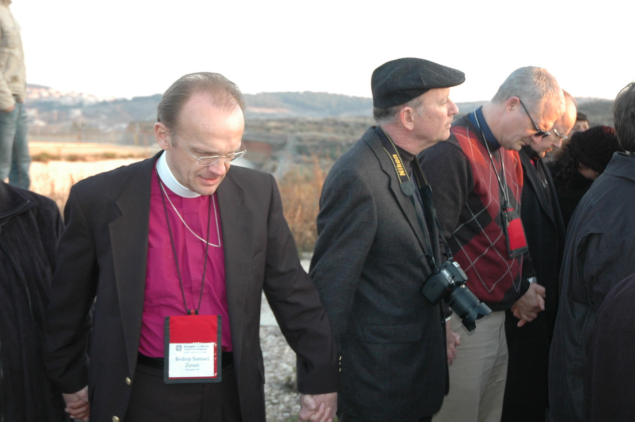Bishop Samuel Zeiser, left, ELCA Northeastern Pennsylvania Synod, holds the hand of Daniel Lehmann, editor of The Lutheran magazine, during prayer time at the Israeli separation barrier, Jan. 12, at Beddo, West Bank.