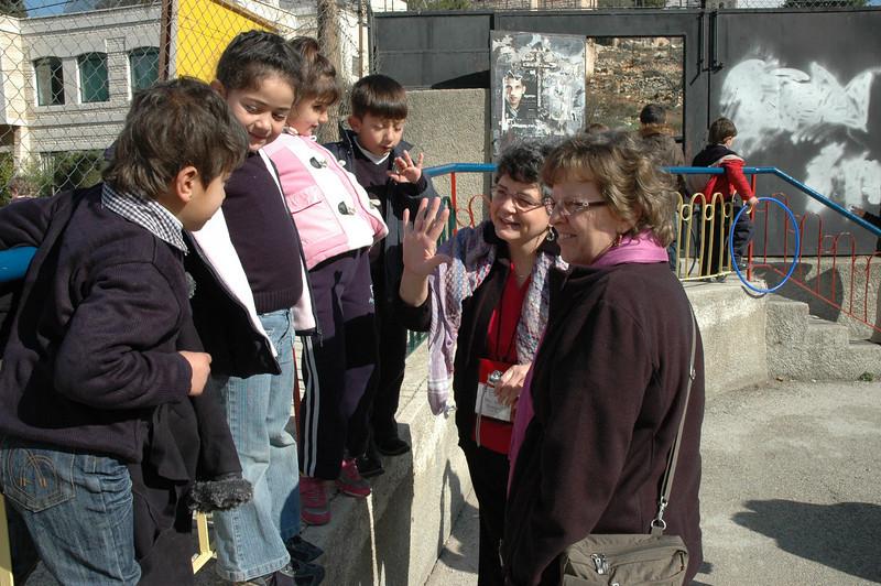 "Deborah Tiemann, right, wife of Bishop Ray Tiemann, ELCA Southwestern Texas Synod, and DeeDee Boerger, wife of Bishop Wm. ""Chris"" Boerger, ELCA Northwest Washington Synod, greet children at Evangelical Lutheran School of Hope, Ramallah, Jan. 12."