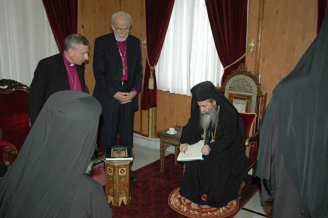 Beatitude Theofilos III, Greek Orthodox Patriarch of Jerusalem, signs a book he presented to ELCA Presiding Bishop Mark Hanson Jan. 9, during a visit to the patriarch in Jerusalem.